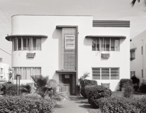 Art deco style house with corner windows, vertical glass block strip, while including pastel colors, and angular geometry.
