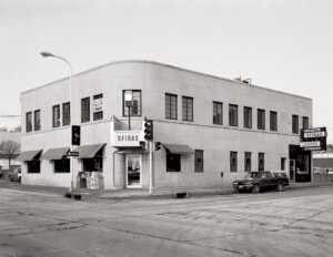 Building on a street corner with a flat roof, smooth walls, featuring art moderne style window canopies.