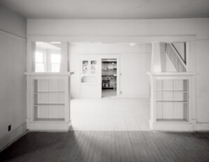 Interior of bungalow style home that has wooden floors, column bases, and has a whitewash kind of color.