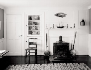 Whitewashed interior featuring cape cod door mouldings accompanied with cabinetry mouldings and decorations on a right justified mantle.