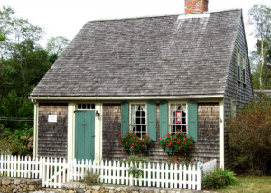 Front view of triangular house with cape cod style shutters and mouldings featuring a white fence with a gate by the front-door.