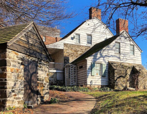 Dutch colonial style house with curved roof with steep slope, mixture of brick and shingle siding, along with window mouldings.