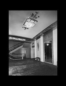Interior of a building which incorporates dark carpet, classical architecture, along with an art deco angular stairway.