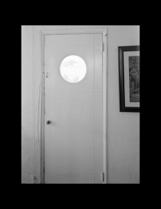 Interior of an art deco style home showcasing a porthole window on the upper portion of an all white door.