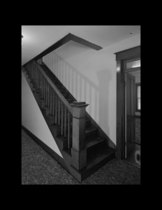Interior of house featuring bungalow style hardwood floor staircase, along with wooden stair mouldings.