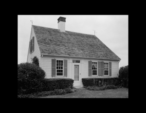 Cape cod style house with symmetrical appearance, shingle siding, and double-hung windows with shutters.