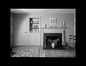 Interior of cape cod style room with door mouldings, cabinetry mouldings, and fireplace mouldings on accent wall.