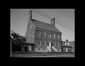 Chesapeake colonial style house with steep roof, two wide chimneys, exterior cornice, and staircase to the front door.