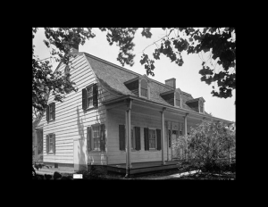 Exterior with dutch colonial style that has gable dormers on roof, window mouldings with shutters, and a covered porch with pillars.