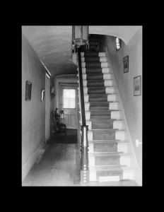 Interior of dutch colonial style home that is facing a hallway with a staircase running up in the hallway.
