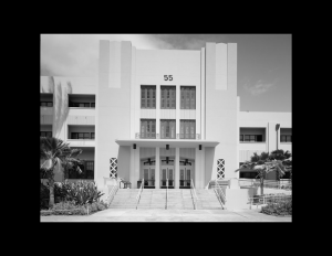 Art moderne style building with front balcony above main doors, along with decorative window panels with repetitive triangular shapes.