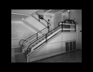Interior of a building featuring an angular staircase with rounded art moderne railings, and shiny art moderne stone floors.