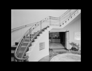 Art moderne building interior showcasing an oval first floor, with a wrap-around staircase along with rounded railings and decorative panels.