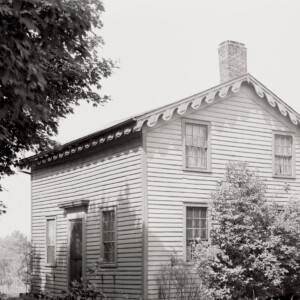 Exterior of Arnold house features shingle siding, window mouldings, cornice mouldings, door mouldings, and an all brick chimney.