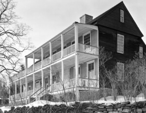 Exterior of new england colonial style building complex featuring a steep roof, and balconies connecting all the rooms accompanied with railing.