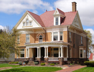 Colonial revival style home with pediment dormer, hipped roof, curved balustrade mouldings accompanied with several columned porticos.