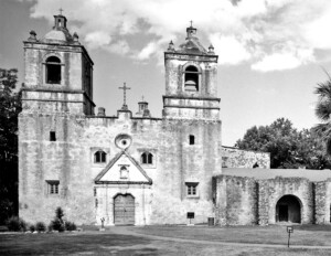 Spanish colonial style building with two side towers, door mouldings, window mouldings, and is made out of stucco-clad.