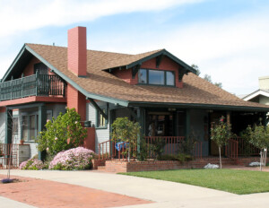 Craftsman style house that features a low overhanging roof with a gable dormer, and a side balcony along with window mouldings.