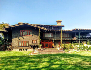 Craftsman style mansion featuring large overhanging roof, window mouldings, enclosed porch with fence, and door mouldings.