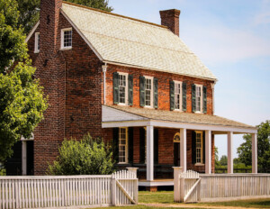All brick farmhouse style home with steep triangular roof, window mouldings with shutters, and a covered porch with columns.