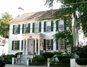Federal style building featuring double-hanging windows, shutters, staircase leading to main door, covered porch with fancy pillars.