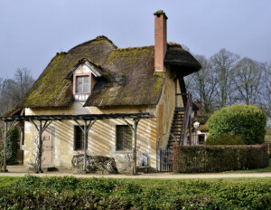 French country style cottage with stone exterior, mossy steep roof with centered gable dormer, one chimney, and outside staircase to second story.