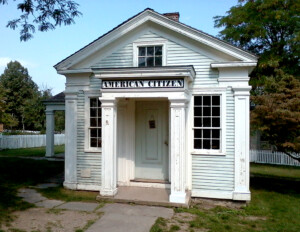 Small greek revival style building with shingle siding featuring a covered porch entrance and window mouldings.
