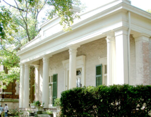 All brick greek revival style building with extensive exterior cornice mouldings, pillars, door mouldings, and windows with shutters.