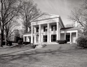 Greek revival style house featuring steps leading to the doorway, windows with shutters, huge pillar mouldings, and triangular roof.