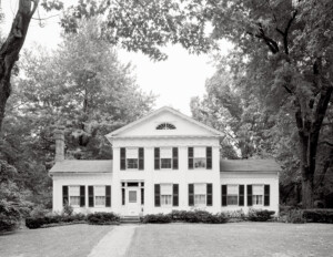 Greek Revival Western Reserve style building with door mouldings, and double hanging windows with shutters.