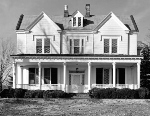 Greek revival style house featuring a dormer, window mouldings, and a covered porch with columns dividing the fence of the porch.
