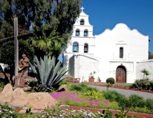 Spanish colonial style building that is all stucco-clad and has many curvy shapes along with many bells.