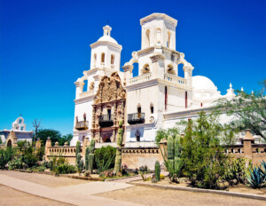 Spanish colonial style building that has balconies, two towers, and is made out of stucco-clad.