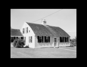 New england colonial style home with double-hanging windows with shutters, door mouldings, and a curved roof with a central chimney.