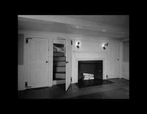 Interior of a new england colonial style room featuring fireplace mouldings, door mouldings, and a hardwood floor.