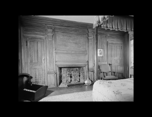 Interior of a new england colonial style bedroom featuring brick fireplace mouldings, door mouldings, and hardwood floor.