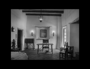 Interior of spanish colonial style room with log beams going across ceiling, clay walls, wooden door mouldings and different room ornaments.
