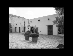 Spanish colonial style complex with stucco-clad walls, door mouldings, and flat roof.