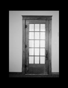Interior of a craftsman style home door featuring door mouldings, and a door knob.