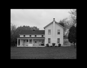 Exterior of farmhouse with side covered ground level porch, two chimneys, slanted triangular roof, and shingle siding.