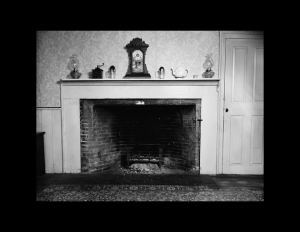 Farmhouse style fireplace featuring fireplace mouldings, and door mouldings.