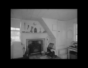 Interior of a farmhouse style room with fireplace mouldings, door mouldings, window mouldings, featuring wooden walls.