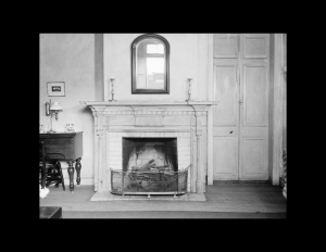Interior of french colonial style room featuring fireplace mouldings, door mouldings, and other room decorations.