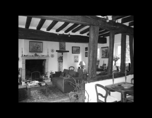 Interior of french country style house featuring exposed wooden ceiling beams, fireplace mouldings, and window mouldings.