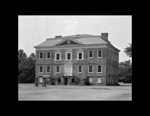 Exterior of brick building with steep roof, winding staircase going to door with mouldings, and window mouldings.