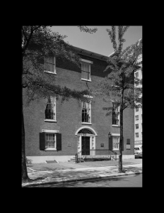 Federal style all brick building featuring windows with shutters, staircase with railing, and door mouldings.