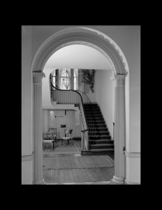 Interior of federal style room showcasing door mouldings, cornice mouldings, and a winding staircase with railing mouldings.