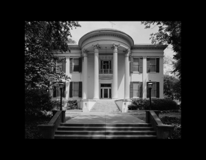 Greek revival style building with oval roof accompanied with huge pillars, and steps leading to the entrance of the building.