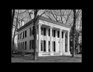 Greek revival style building with exterior cornice mouldings, huge pillars, steps leading to the entrance, and windows with shutters.