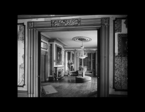 Interior of greek revival style room featuring hardwood floors, house decoration, door mouldings, and interior cornice mouldings.